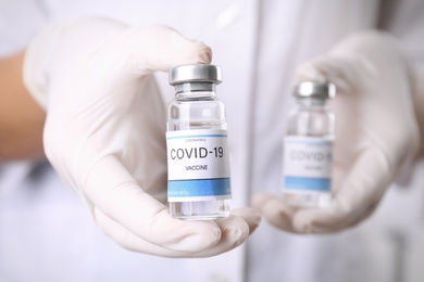 Doctor holding vials with vaccine against Covid-19, closeup