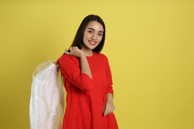 Young woman holding hanger with shirt in plastic bag on yellow background. Dry-cleaning service