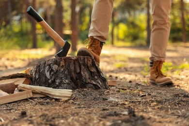 Man near tree stump with axe in forest, closeup of legs