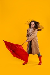 Emotional woman with umbrella caught in gust of wind on yellow background