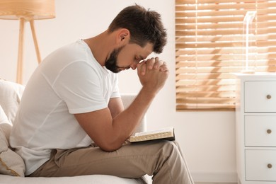 Religious man with Bible praying indoors. Space for text
