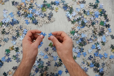 Man playing with puzzles on floor, top view