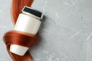 Bottle wrapped in lock of hair on light grey marble background, top view with space for text. Natural cosmetic product