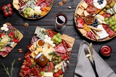 Assorted appetizers served on black wooden table, flat lay