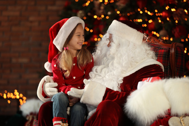 Santa Claus and little girl near Christmas tree indoors