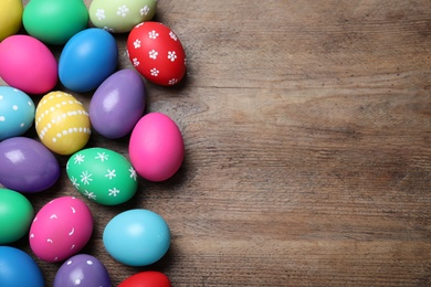 Colorful eggs on wooden background, flat lay with space for text. Happy Easter