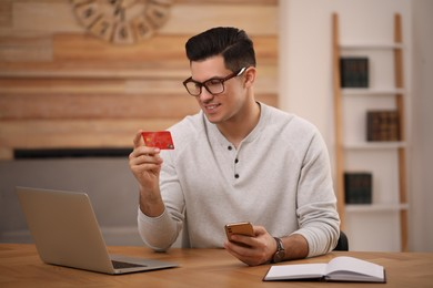 Man using smartphone and credit card for online payment at desk in room