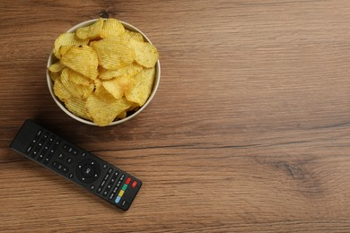 Modern tv remote control and chips on wooden table, flat lay. Space for text