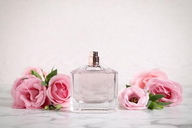 Bottle of perfume and beautiful flowers on white marble table