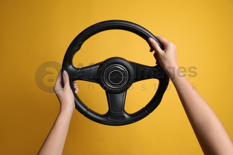 Woman holding steering wheel on yellow background, closeup