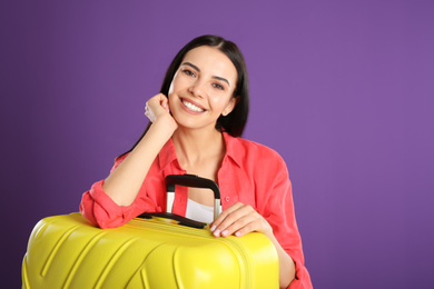 Beautiful woman with suitcase for summer trip on purple background. Vacation travel