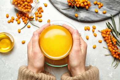 Woman holding cup with sea buckthorn tea at grey table, top view