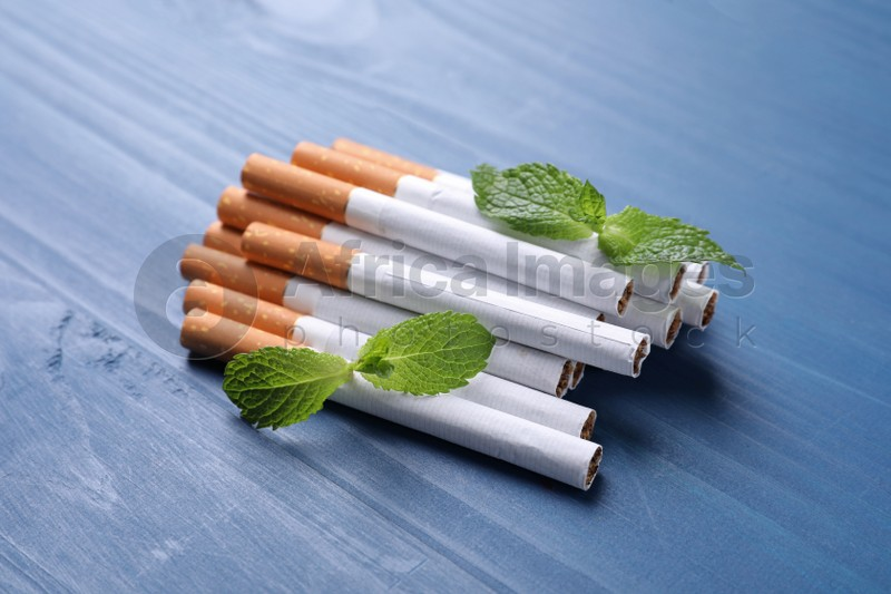 Menthol cigarettes and mint leaves on blue wooden table