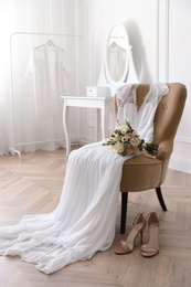 Elegant wedding dress, shoes and bouquet in room