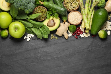 Flat lay composition with different vegetables, seeds and fruits on black table, space for text. Healthy diet