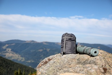 Sleeping bag and camping mat on mountain peak, space for text