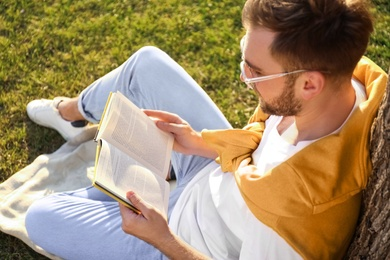 Young man reading book on green grass near tree in park