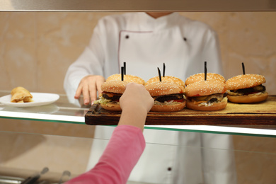 Little girl taking burger at serving line in canteen. School food
