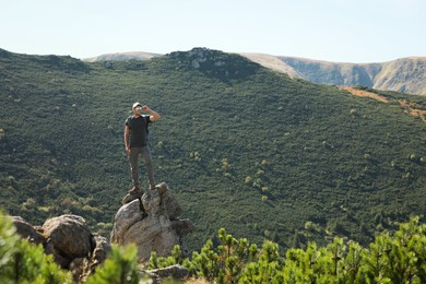 Man with backpack standing on rocky peak. Mountain tourism