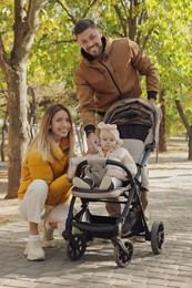 Happy parents walking with their baby in stroller at park on sunny day