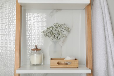 Silicone vase with flowers on white marble wall and shelving unit in stylish bathroom