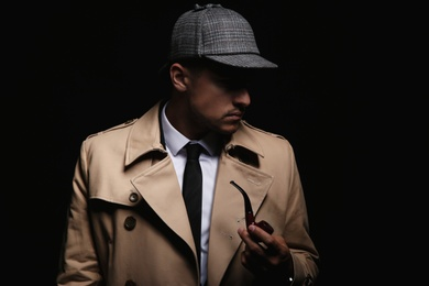 Old fashioned detective with smoking pipe on dark background