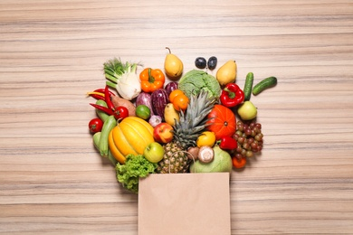 Paper bag with assortment of fresh organic fruits and vegetables on wooden table, flat lay