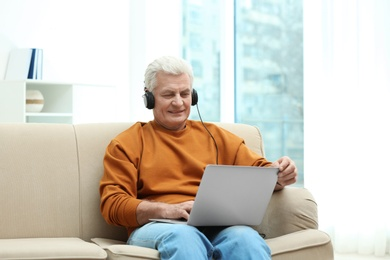 Portrait of mature man with laptop and headphones on sofa indoors