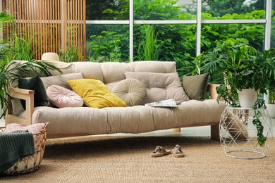 Indoor terrace interior with comfortable sofa and green plants
