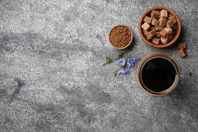 Glass cup of delicious chicory drink, granules, brown sugar and flowers on grey table, flat lay. Space for text