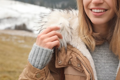 Young woman in warm clothes near snowy hill, closeup. Winter vacation