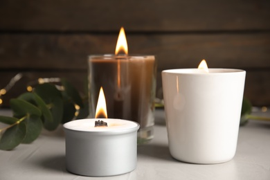 Burning scented candles on light grey table