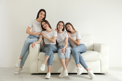 Beautiful young ladies in jeans and white t-shirts on sofa indoors. Woman's Day