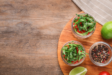 Healthy salad in glass jars on wooden table, flat lay. Space for text