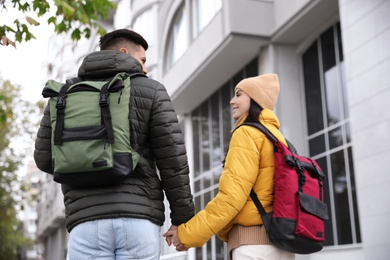 Couple with travel backpacks on city street, back view. Urban trip