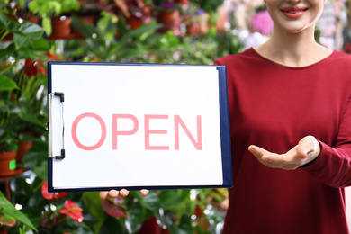 Female business owner holding OPEN sign in flower shop, closeup