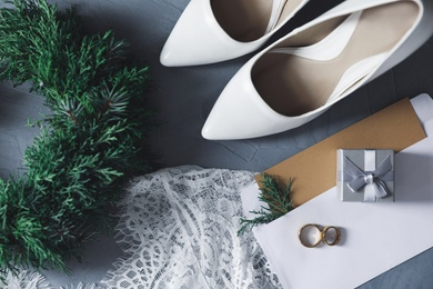 Flat lay composition with wedding dress, white high heel shoes and rings on grey background