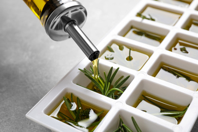 Pouring olive oil into ice cube tray with fresh rosemary at grey table, closeup