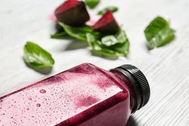 Bottle of beet smoothie on table, closeup