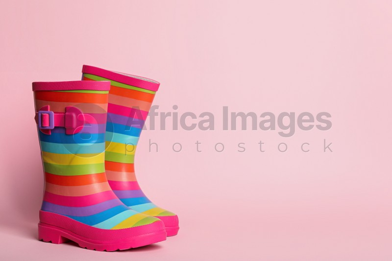 Pair of striped rubber boots on pink background. Space for text