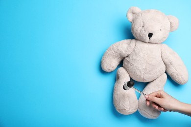 Woman pretending to test teddy bear's reflexes with hammer on light blue background, closeup and space for text. Nervous system diagnostic