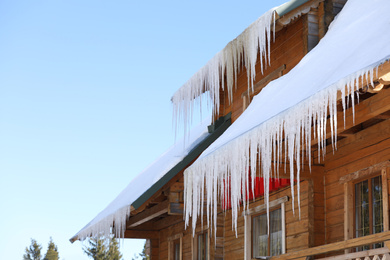 House with icicles on roof. Winter season
