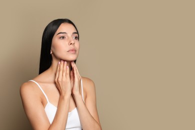 Young woman doing thyroid self examination on beige background. Space for text