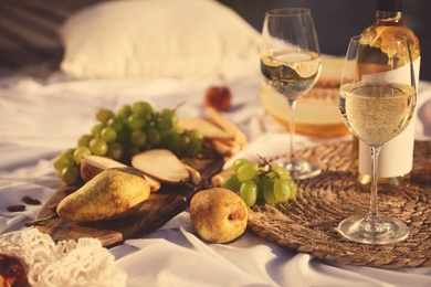 Delicious food and wine on white picnic blanket