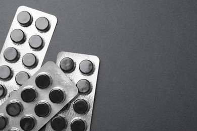 Activated charcoal pills in blisters on black background, flat lay with space for text. Potent sorbent