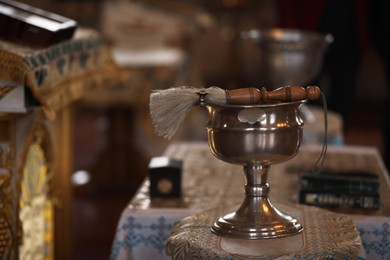 Silver vessel with holy water and brush on stand in church, space for text. Baptism ceremony