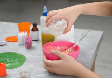 Little girl adding sparkles into homemade slime toy at table, closeup of hands