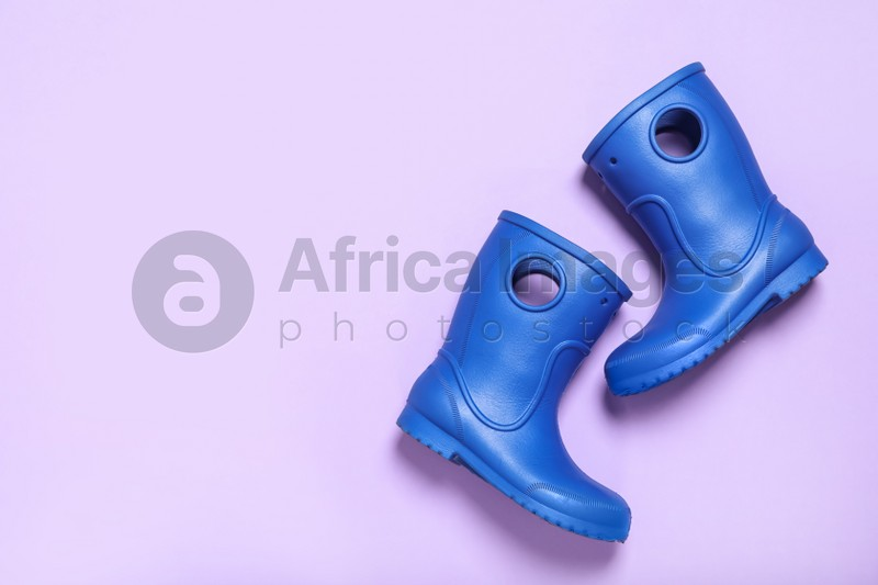 Pair of blue rubber boots on light background top view. Space for text