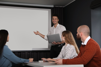 Business people listening to speaker in conference room with video projection screen