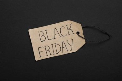 Black Friday tag on color background, top view